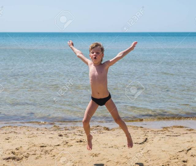 Six Year Old Boy In Black Speedo Jumping Into The Sea And Shouts