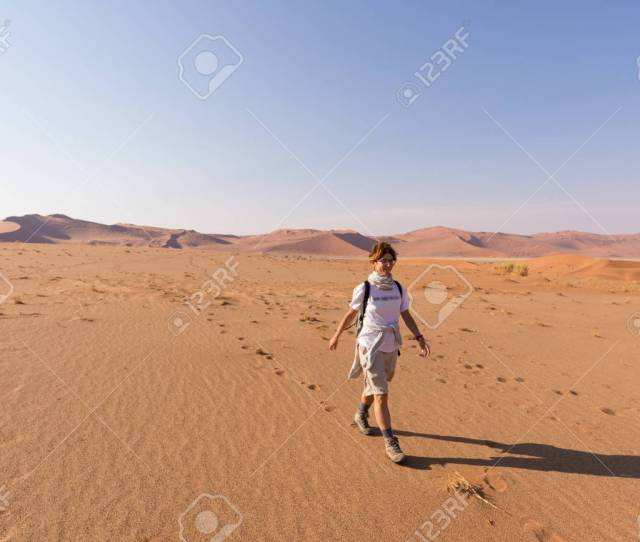 Stock Photo Tourist Walking On The Scenic Dunes Of Sossusvlei Namib Desert Namib Naukluft National Park Namibia Adventure And Exploration In Africa