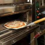 Putting Pizza In Oven At Restaurant Kitchen Stock Photo Picture And Royalty Free Image Image 18877346