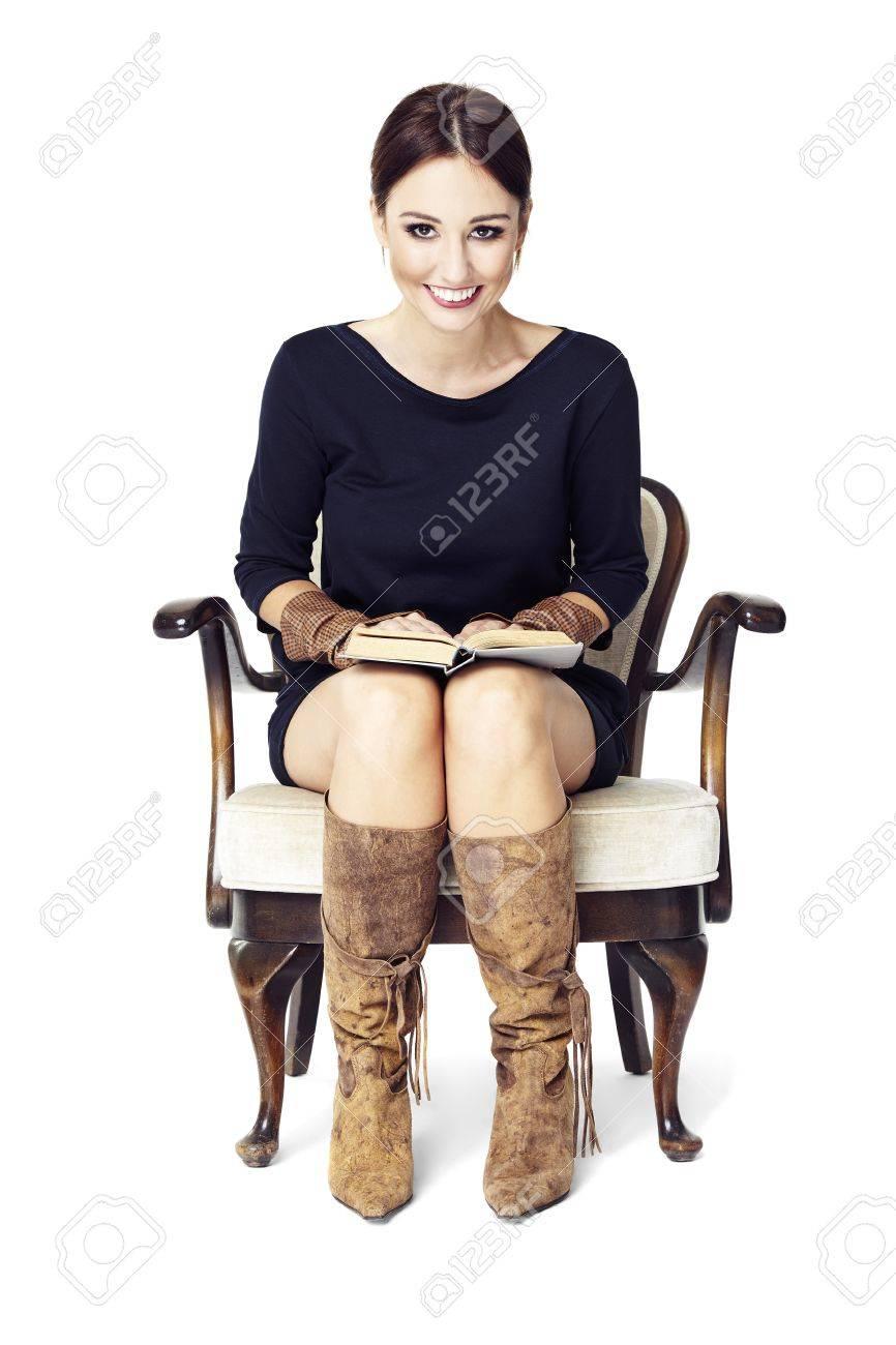 belle jeune femme assise sur un fauteuil lisant un livre et souriant a moi banque d images et photos libres de droits image 51852867