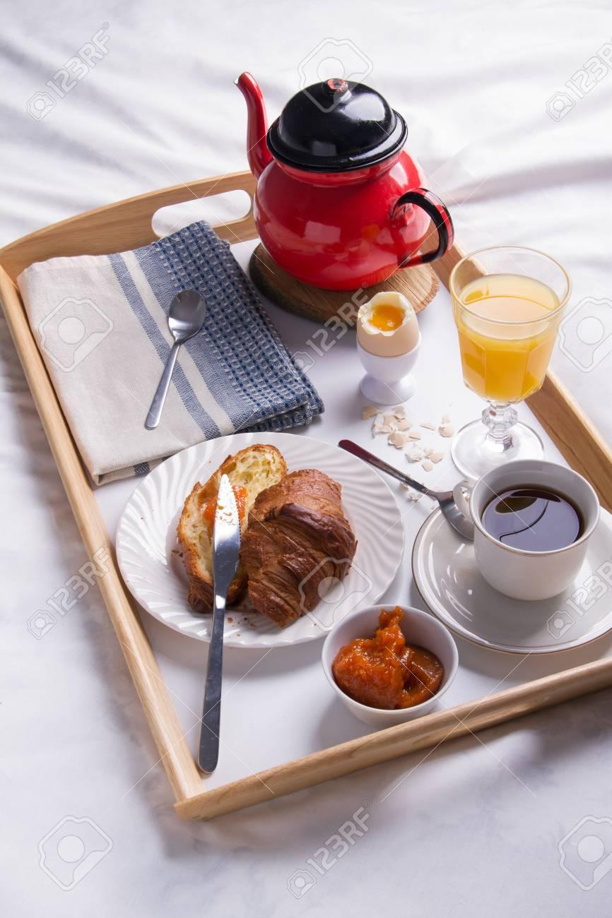 petit dejeuner romantique dans le lit sur un plateau en bois