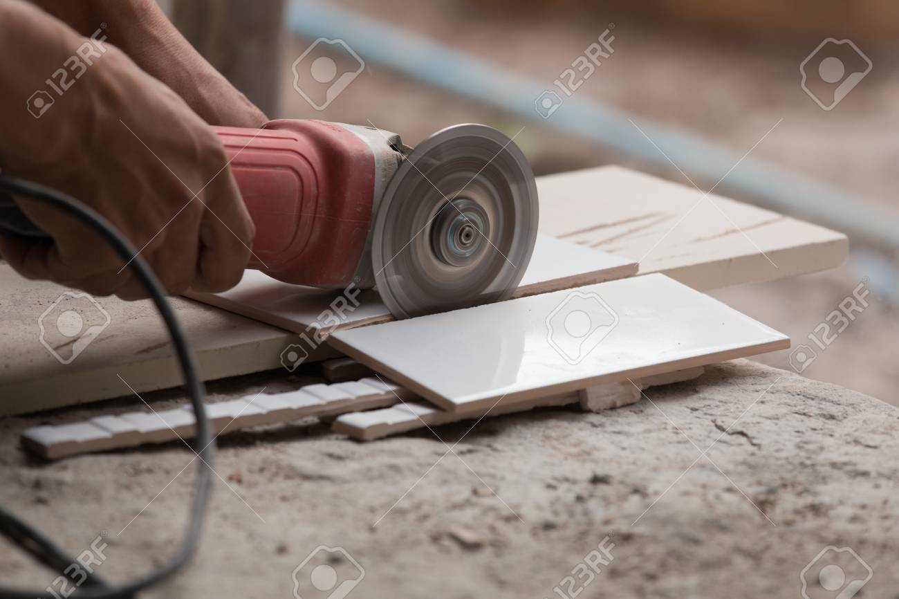 worker cutting a tile using an angle grinder at construction