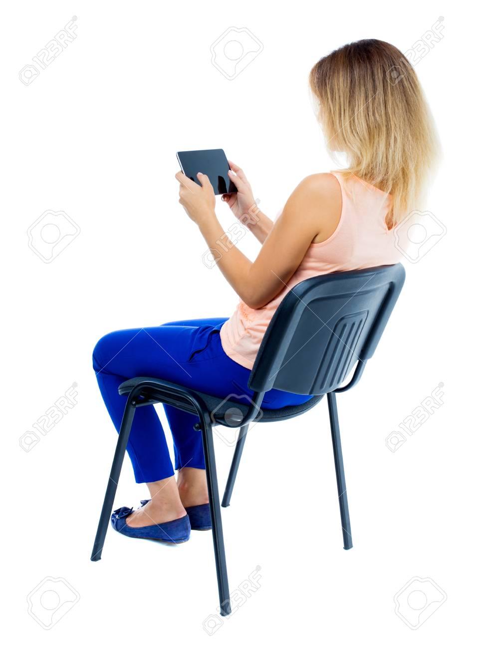 vue arriere de la femme assise sur une chaise et regarde l ecran de la tablette collection de personnes vue arriere vue arriere de la personne isole sur fond blanc blonde en pantalon