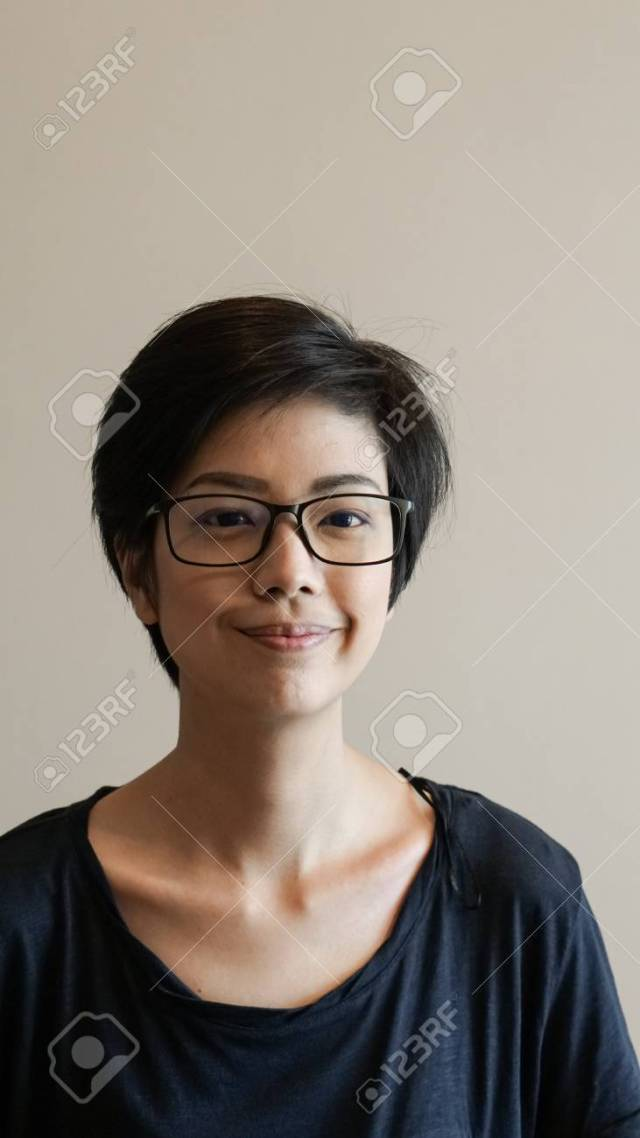 casual asian woman with short hair and glasses on color background