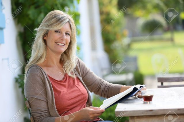 Mature Woman Reading Book In Backyard Stock Photo 32046966