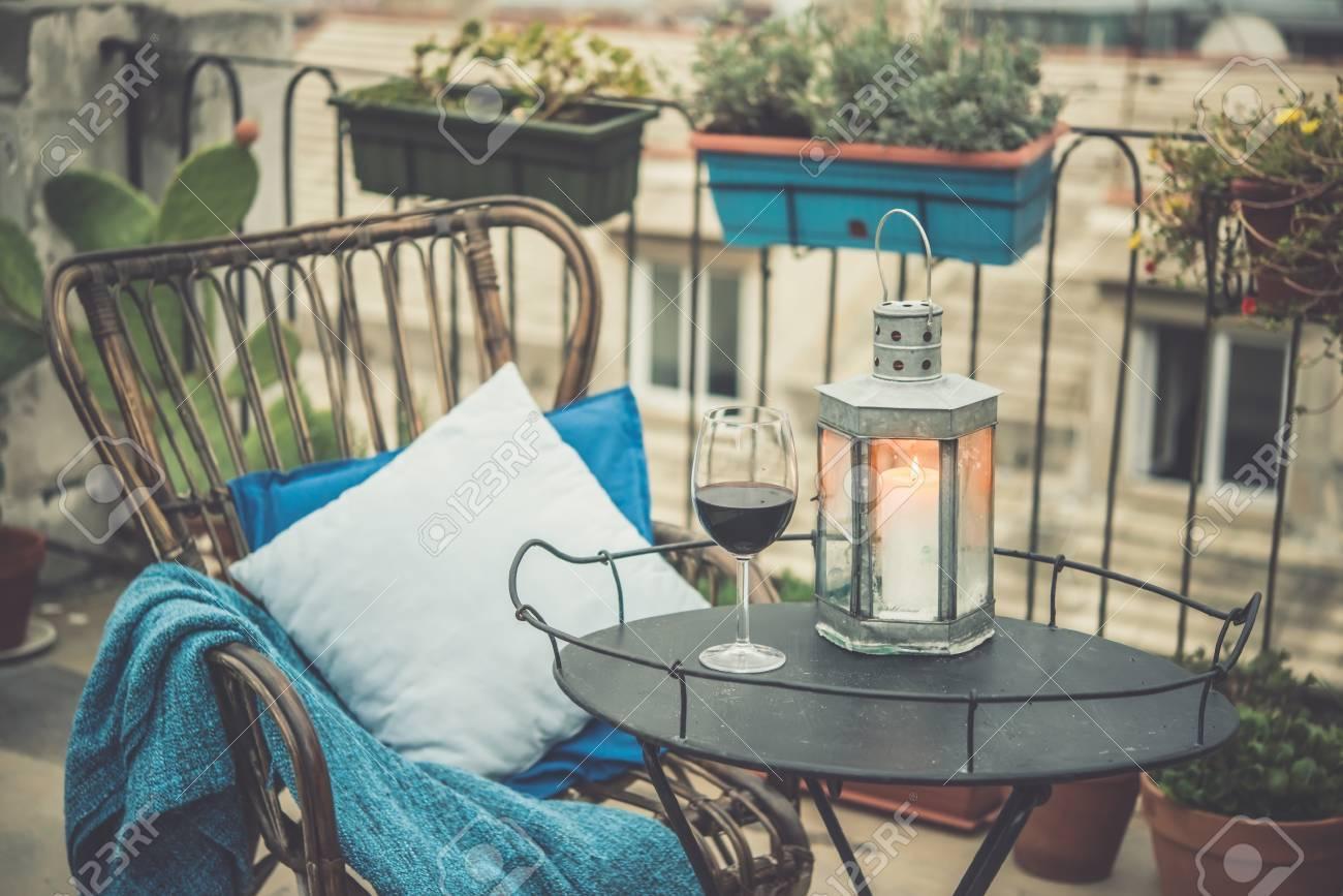 belle terrasse ou balcon avec un confortable fauteuil en rotin et un verre a vin sur une petite table en fer image tonifiee