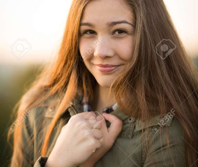 Portrait Of A Beautiful Teen Girl With Long Hair Wearing A Thick Winter Coat Holding It