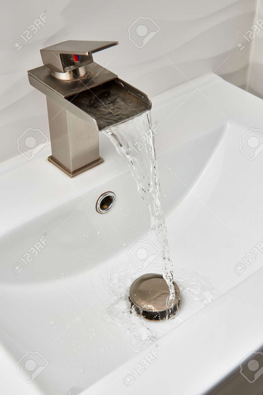 running water from brushed nickel faucet on top of the white