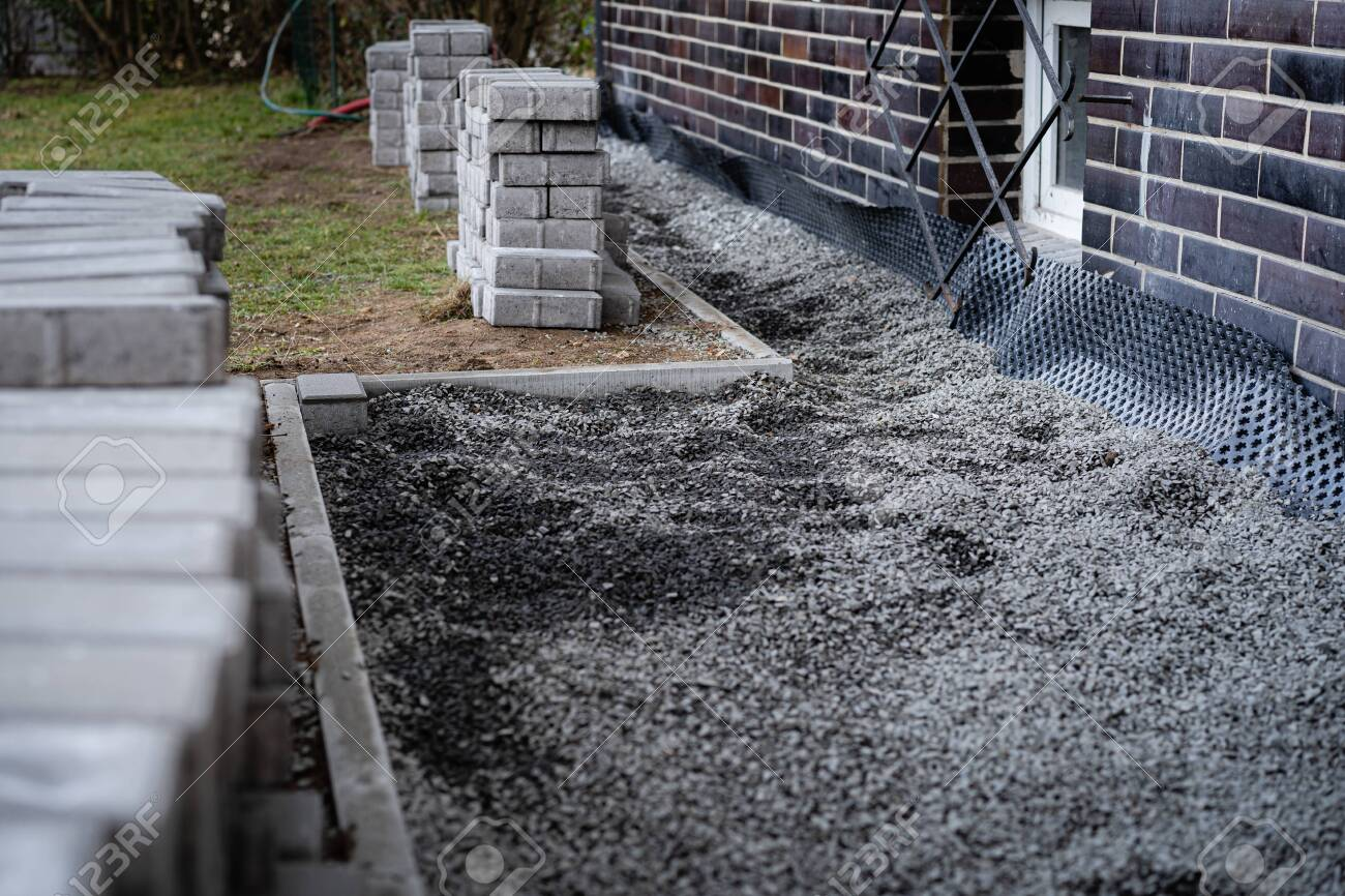 laying gray concrete paving slabs along a house walkway stacks stock photo picture and royalty free image image 141383248