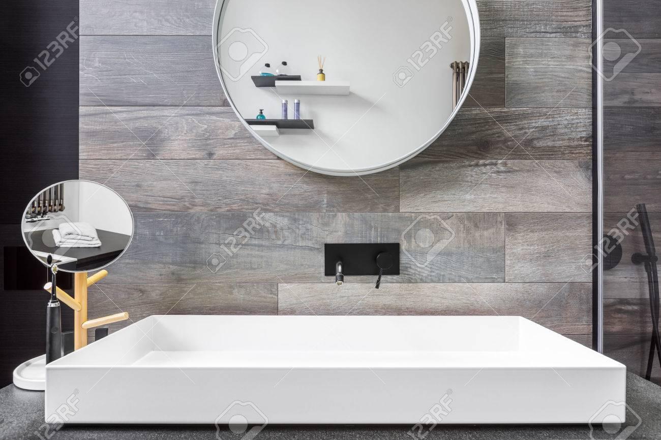 bathroom with countertop washbasin mirror and grey tiles