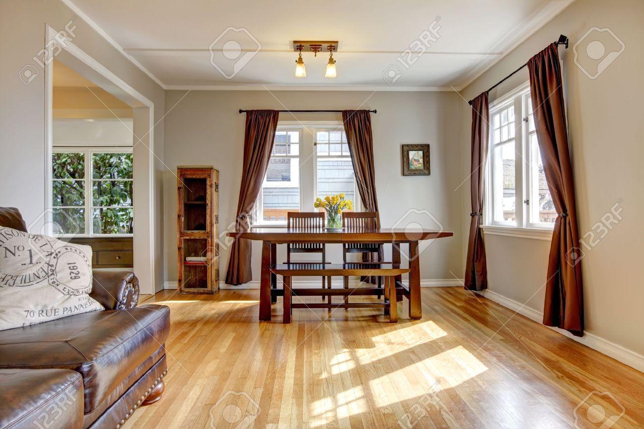 salle a manger avec rideau brun et plancher de bois franc et canape en cuir