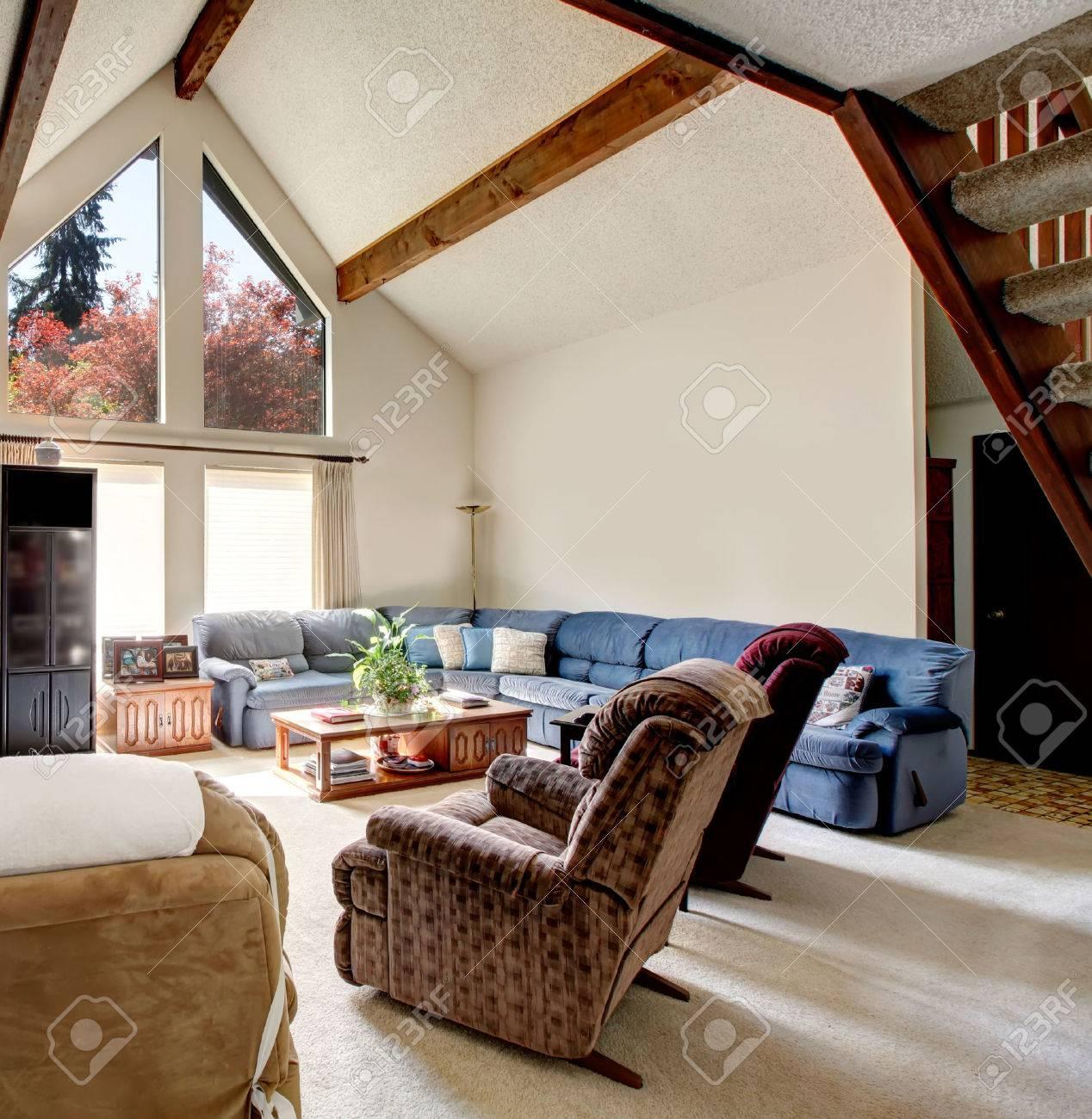 lumineux grand salon avec plafond voute et poutres tapis de sol rocheux desing mur meuble avec canape vaste ensemble des chaises une table basse
