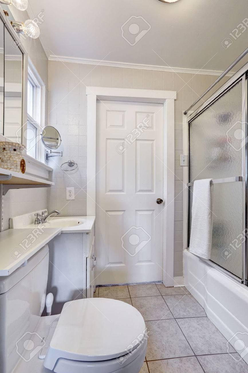 petit interieur de salle de bain blanche avec porte de douche en verre