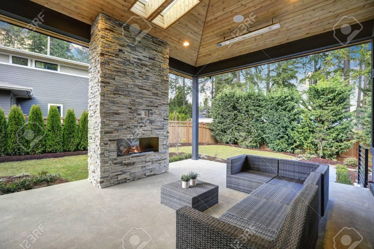 schicke elegante deck patio design features gewolbt verkleidete decke mit oberlichtern uber einen boden zu decke grau stein kamin und grosse taupe korbweide sofa mit ottomane als couchtisch nordwest usa lizenzfreie fotos