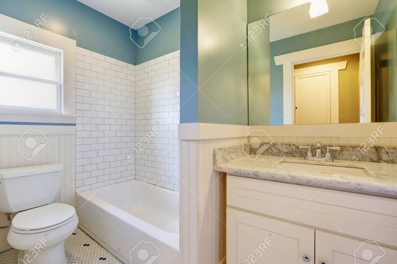 white and blue bathroom with vintage tile and a carrera marble topped