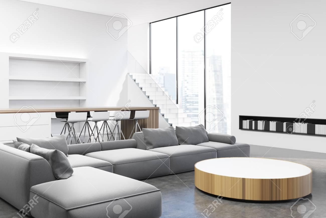 interieur de salon blanc et gris avec une table ronde des canapes et des fauteuils gris clair a proximite de grandes fenetres et des etageres coin