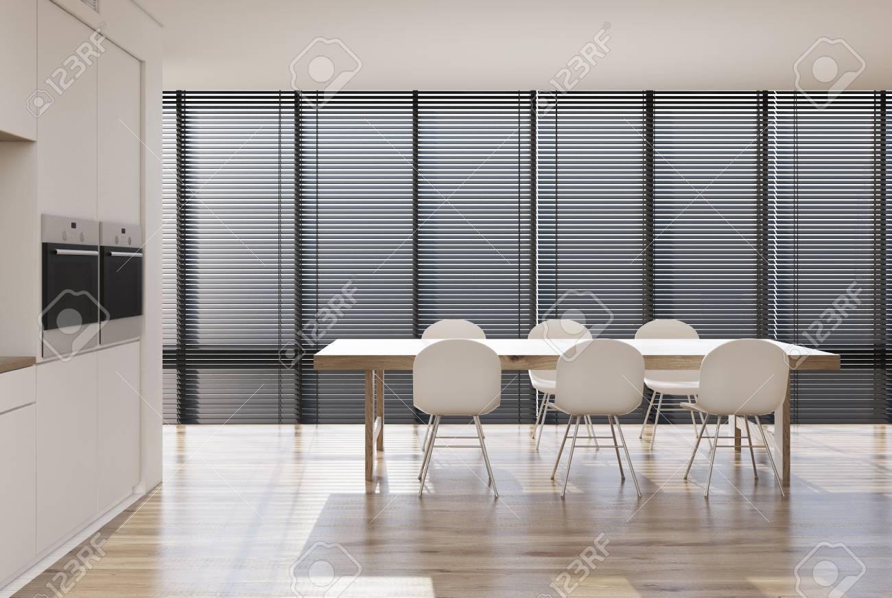 interieur de cuisine blanc avec baie vitree stores une longue table entouree de chaises blanches un comptoir et deux poeles encastres rendu 3d