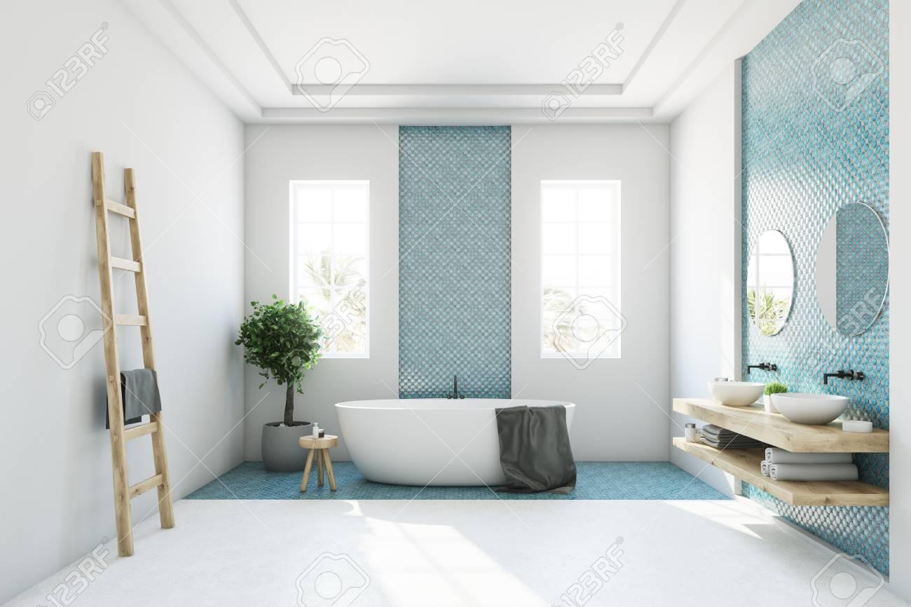 interieur de salle de bain blanc et bleu avec une baignoire ronde blanche deux fenetres etroites un arbre dans une casserole et une echelle dans un