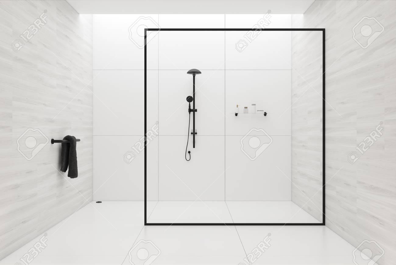 interieur de salle de bain en carrelage blanc avec un sol carrele blanc une serviette noire dans le coin et une douche noire derriere un mur de