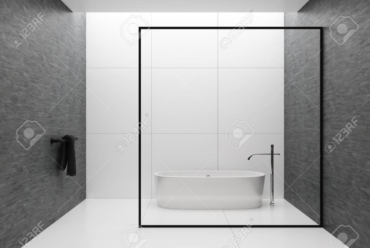 carrelage blanc et interieur de salle de bains avec mur gris sol en carrelage blanc serviette noire dans le coin et baignoire blanche derriere un