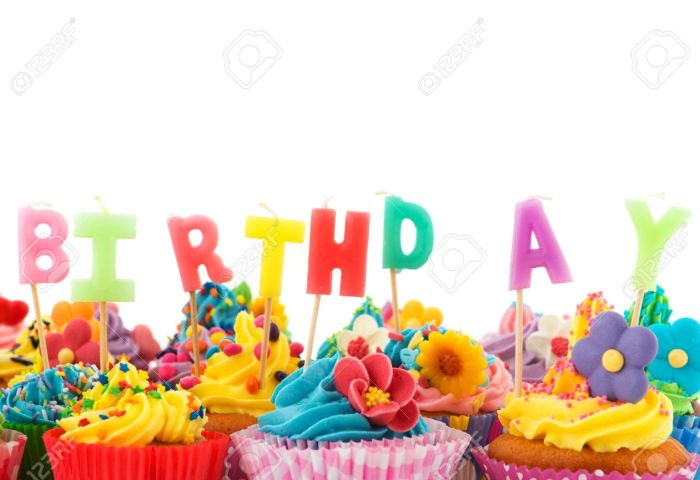 Colorful Birthday Cupcakes With Candles Isolated Over White
