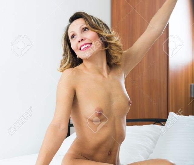 Smiling Middle Aged Nude Woman Stretching In Bedroom Stock Photo 34628203
