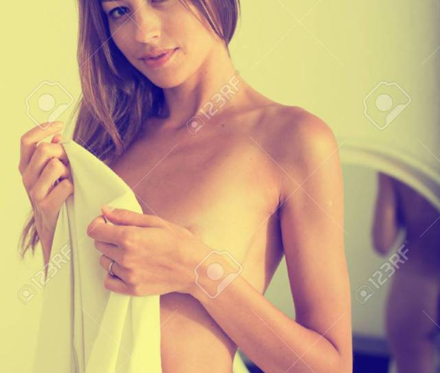 Portrait Of Young Woman Without Clothes Standing And Covering Herself With Sheet In Bedroom Stock Photo