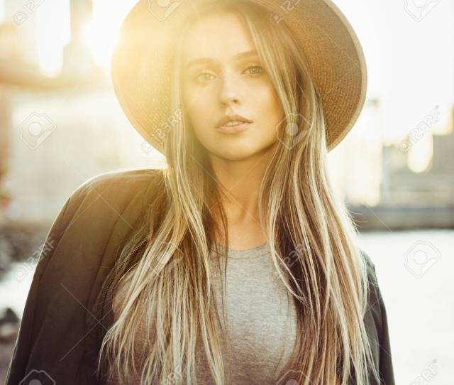 Beautiful Blonde Girl With Long Hair Wearing Hat At Sunset Time In City Stock Photo