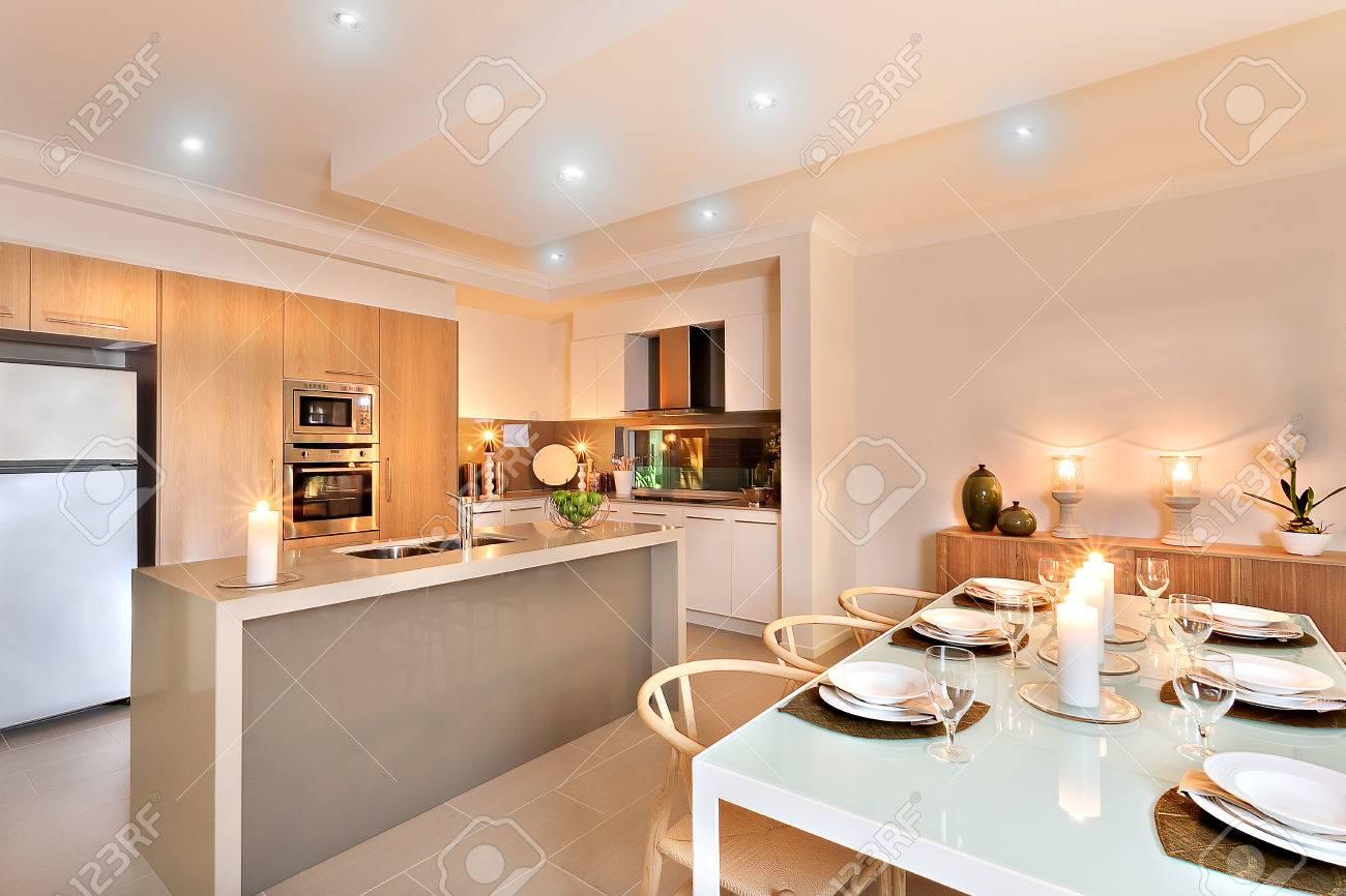 cuisine moderne avec refrigerateur blanc a cote du four mural entoure de placards en bois bien prepares pour servir avec des bougies clignotantes sur le comptoir et a la table du diner