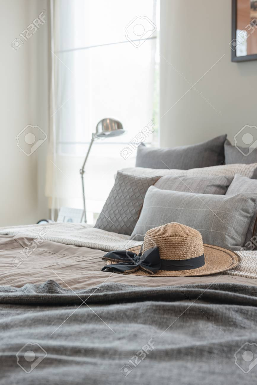 Contemporary Style Bedroom With Earth Tone Color Hat And Pillows