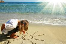 Little Girl Draw The Sun On The Sand On The Beach Stock Photo ...