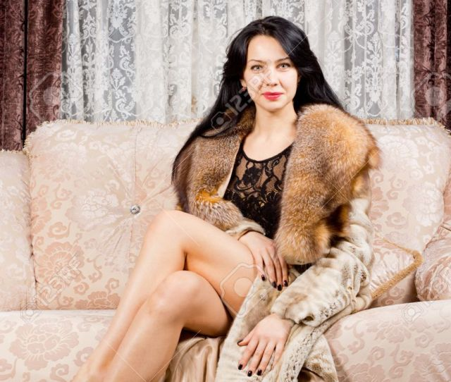 Glamorous Smiling Sophisticated Woman Posing On A Sofa With Her Long Bare Legs Crossed In An
