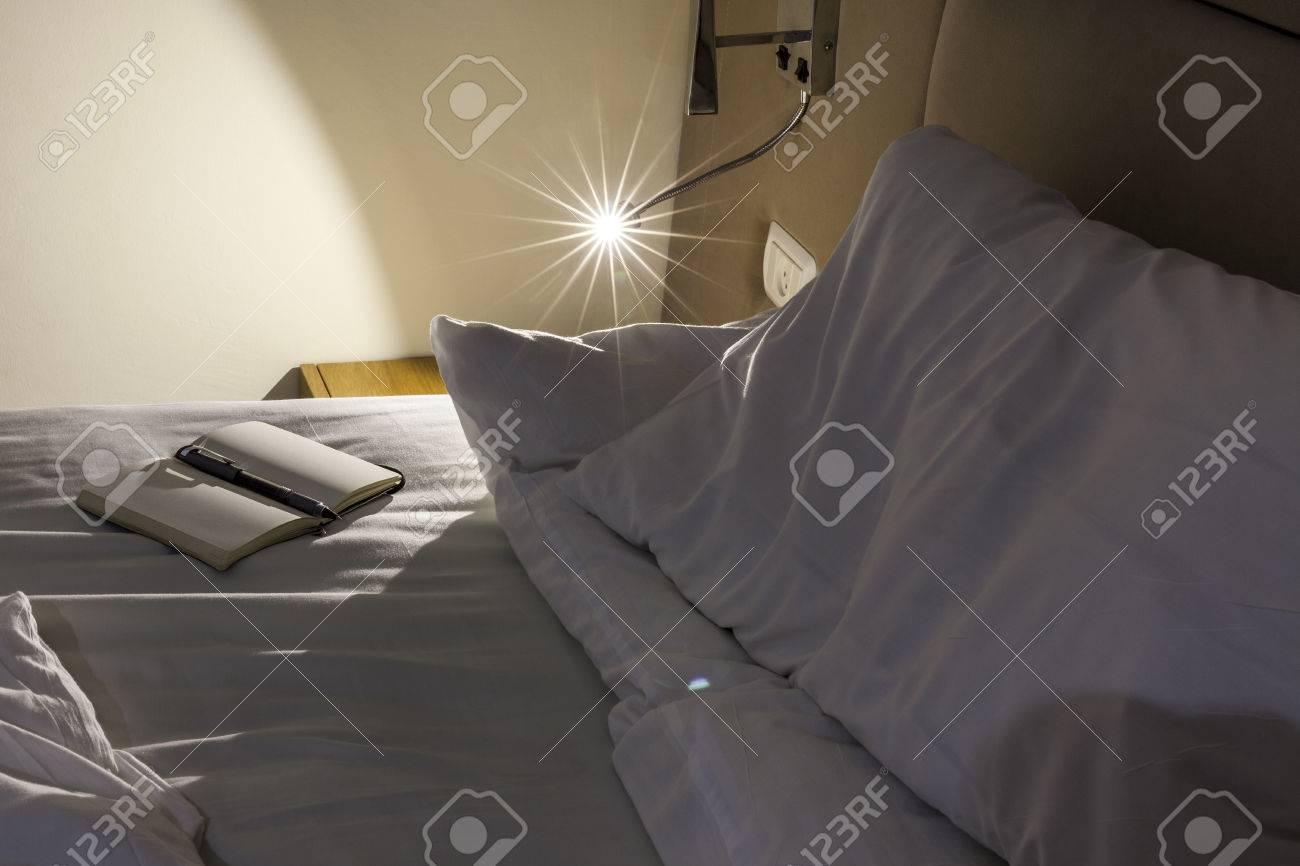 banque d images lit messed avec des draps blancs avec la lumiere de lecture sous tension et bloc notes avec un stylo a cote de l oreiller et de nuit