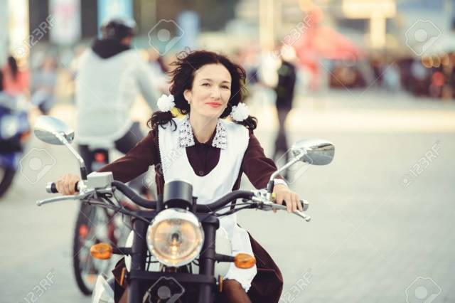 beautiful young woman, hairstyle and bows outdoors with a motorcycle