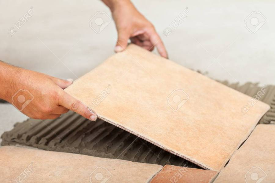 Laying Ceramic Floor Tiles   Man Hands Fitting The Next Piece     Laying ceramic floor tiles   man hands fitting the next piece  closeup  Stock Photo