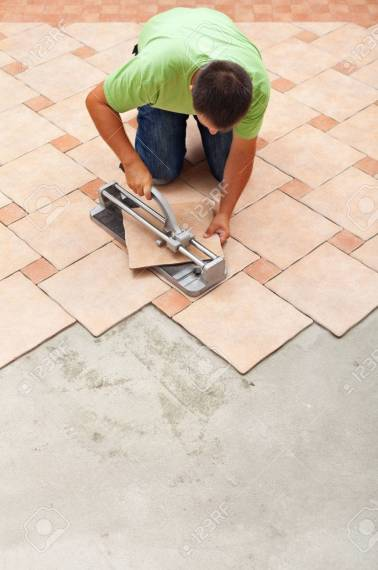 Man Cutting Ceramic Floor Tiles With Manual Cutter   Knealing     Man cutting ceramic floor tiles with manual cutter   knealing on the  already completed surface