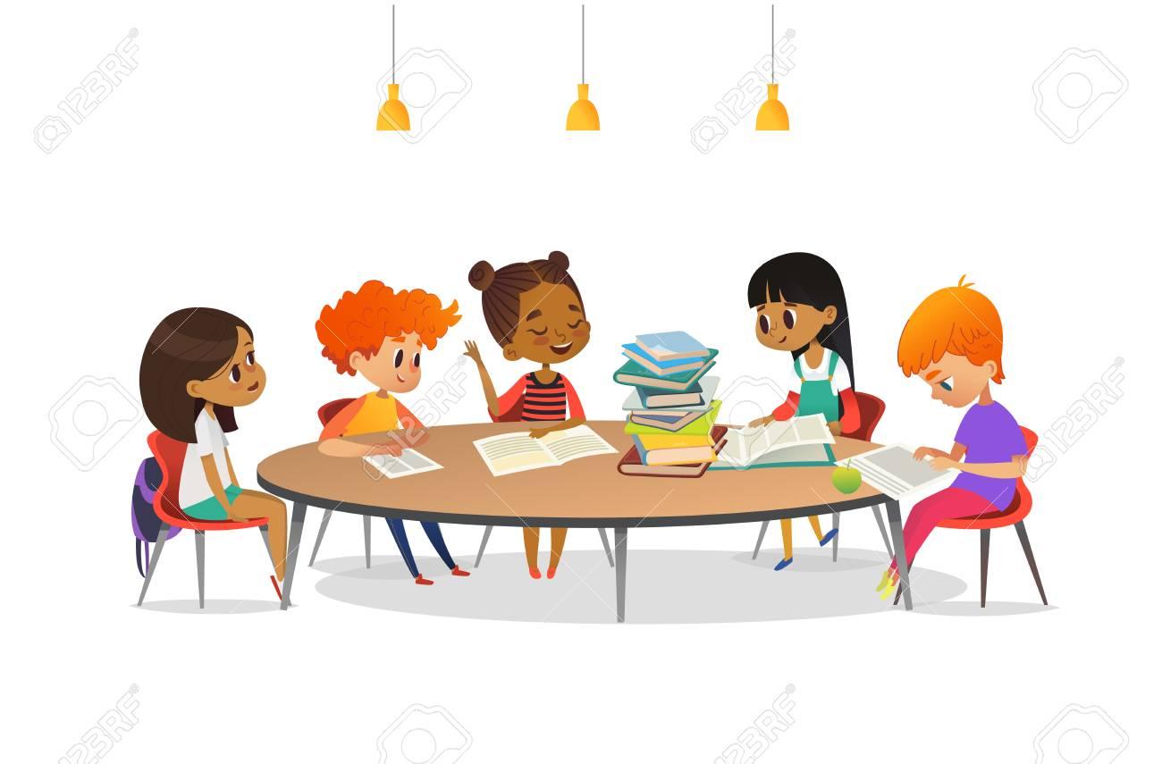 des enfants multiraciaux assis autour de la table ronde avec des tas de livres dessus et ecoutant une fille qui lit a voix haute club de litterature