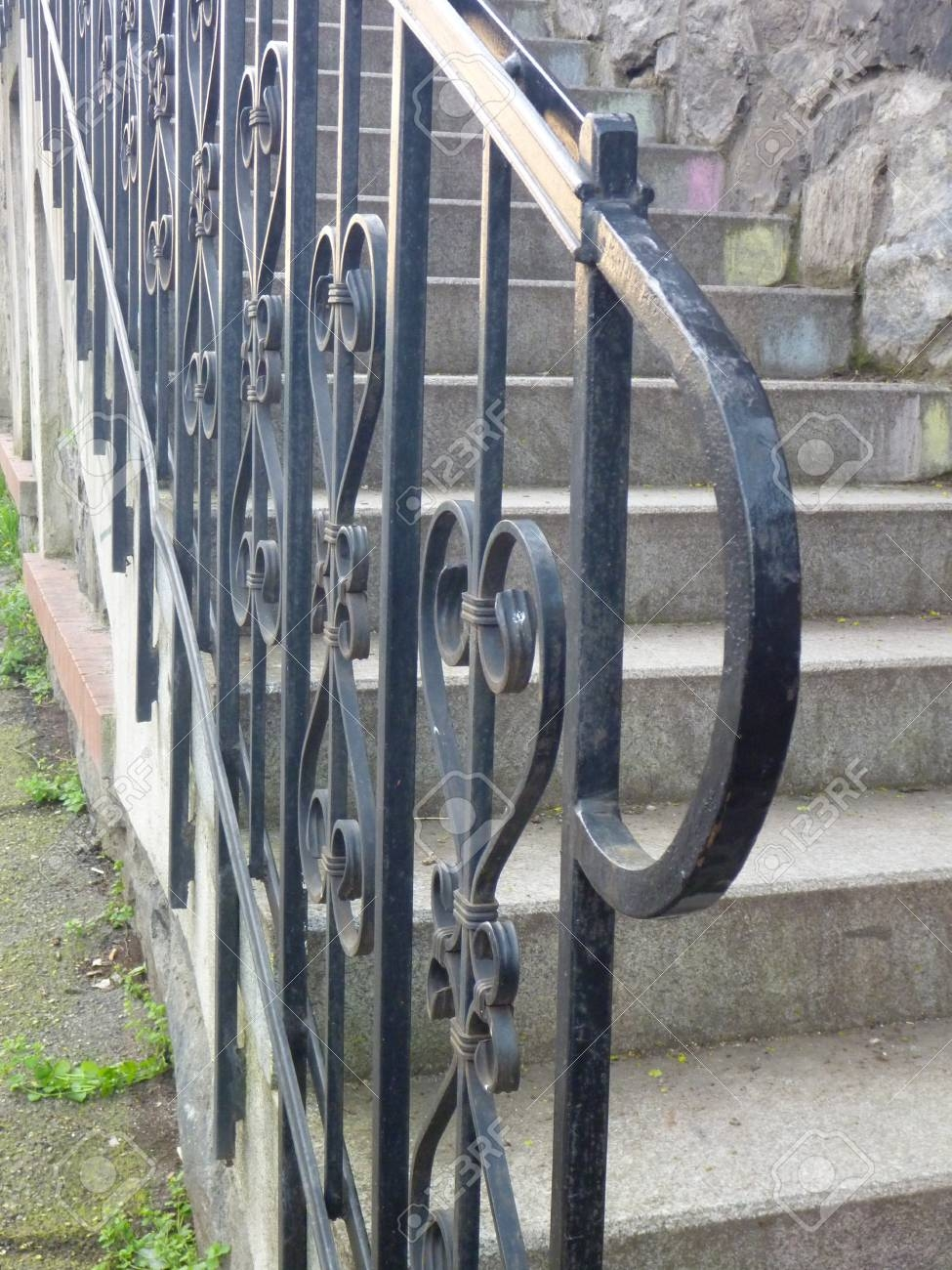 A Detail Of Curved Metal Railing At Outdoor Stairs Stock Photo | Metal Railings For Outdoor Steps | Railing Ideas | Front Porch Railings | Concrete Steps | Wrought Iron Railings | Railing Kits