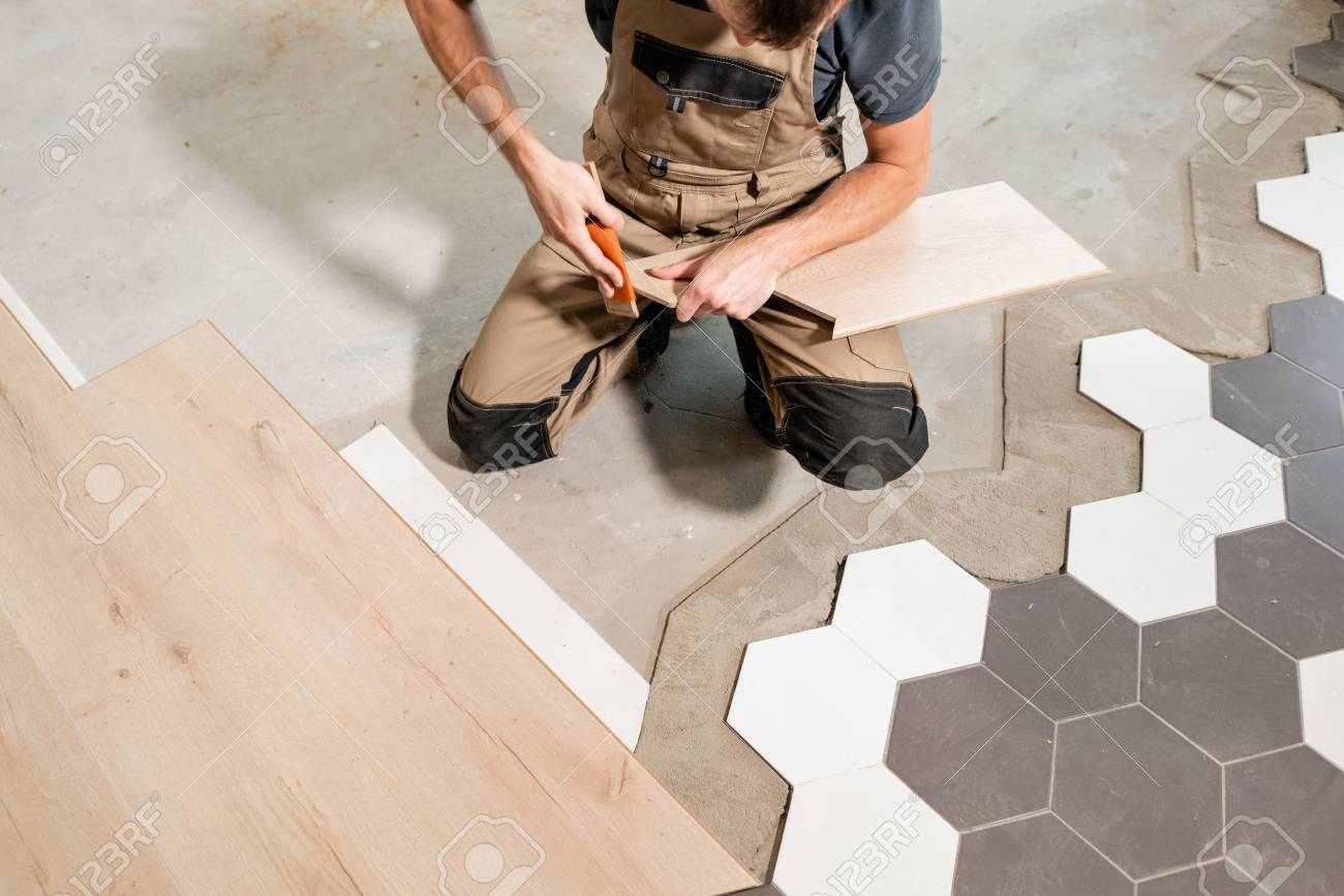 male worker installing new wooden laminate flooring the combination