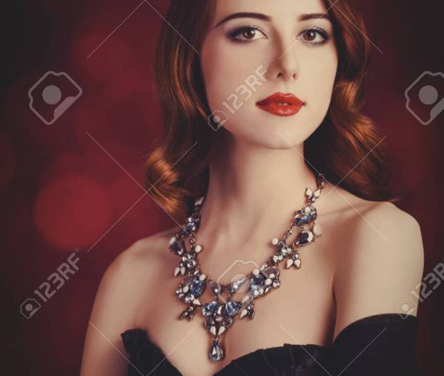 Portrait Of A Beautiful Girl In Retro Corset And Nakelace On Red Background Stock Photo