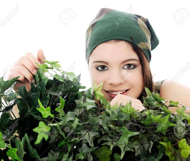 A Beautiful Teen Girl In Camouflage Smiling Behind Thick Foliate On A White Background