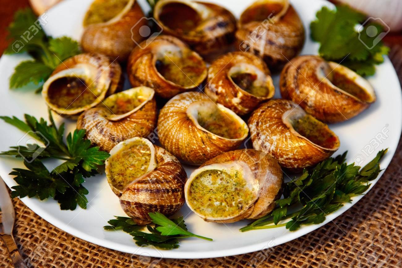 escargots de bourgogne schnecken mit krauterbutter gourmet teller in franzosisch traditionelle mit petersilie und brot auf weissem teller