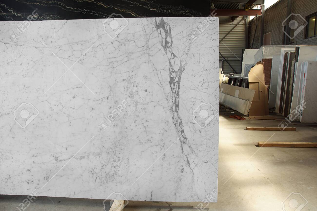 a slab of natural white marble with gray veins in a stone warehouse