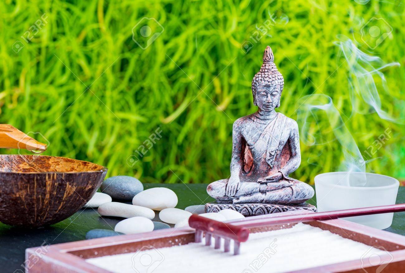 fond de jardin zen avec bouddha bougies rateau pierres de sable et de zen