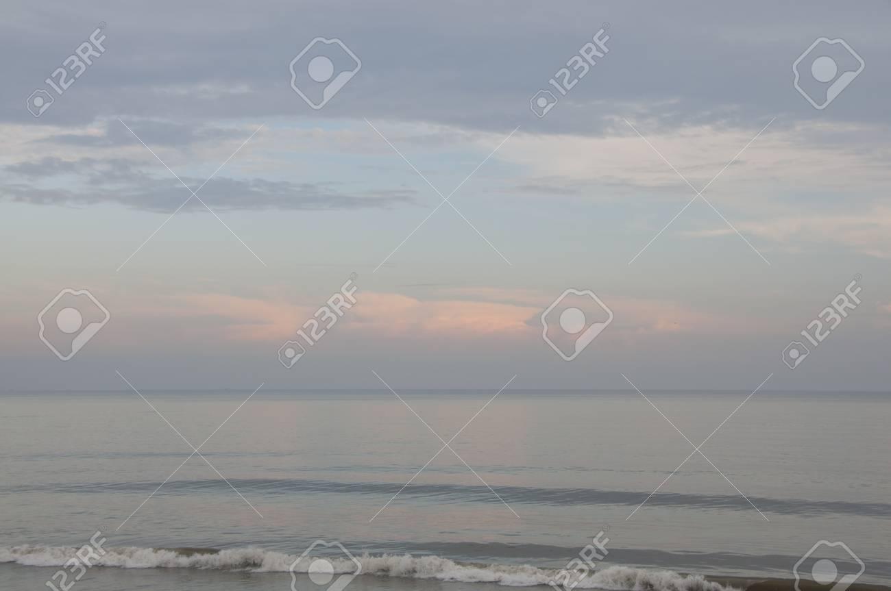 banque d images vague deferlante calme et tranquille sur une plage deserte avec des nuages roses et bleu en arriere plan