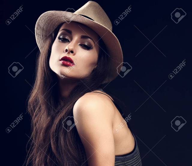 Beautiful Sexy Female Model In Cowboy Summer Hat And Hot Red Lips On Dark Background Posing