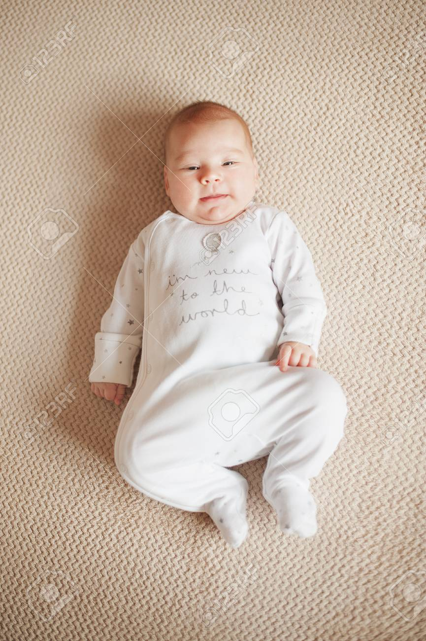 pretty baby in a white pajamas lying on his back. flat lay stock