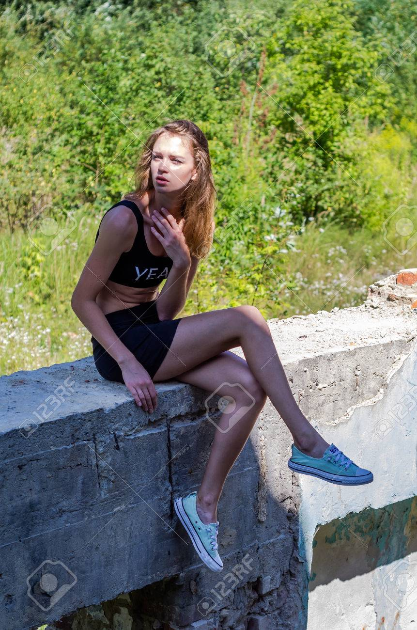Young Charming Sexy Teen Girl With Long Hair In A Short Mini Skirt And Tank Top Sexy Sitting Among The Ruins On A Concrete Slab At An Abandoned