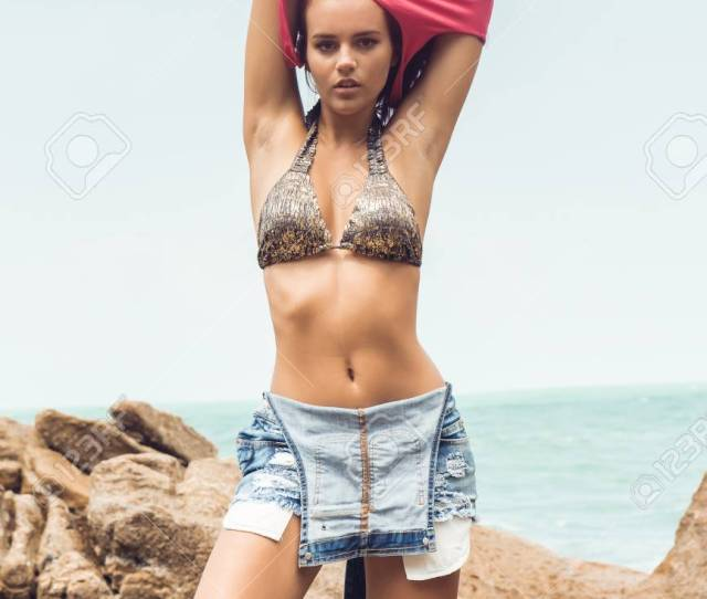 Sexy Girl In Pink T Shirt And Denim Overall Undress On Rock Beach Sea Ocean