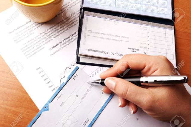 Womans Hand Writing A Check - Close Up Stock Photo, Picture And
